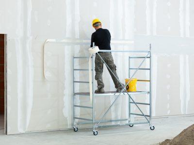 pracownik tynkuje ścianę